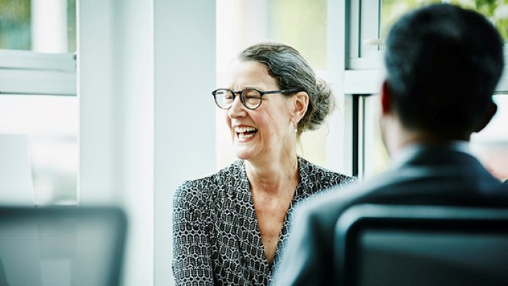 Older woman laughing in meeting