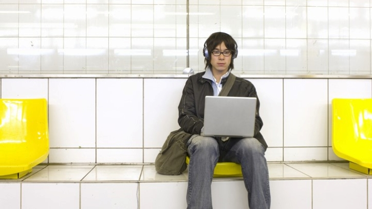 Young man sitting on bench with computer and headphones