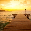 Woman standing on dock at sunset