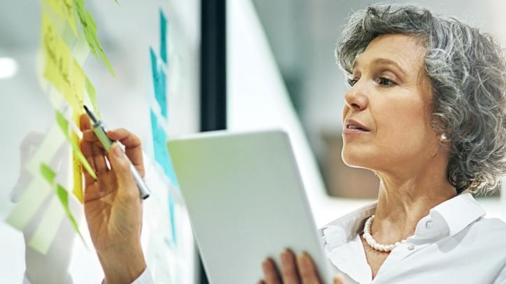 Woman with tablet standing at whiteboard