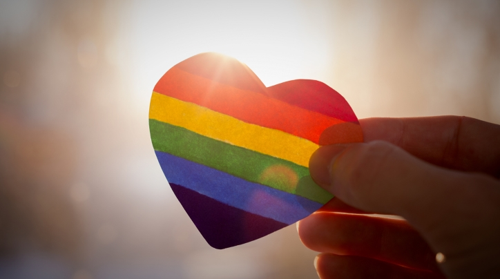 Fingers holding rainbow heart up to sunlight