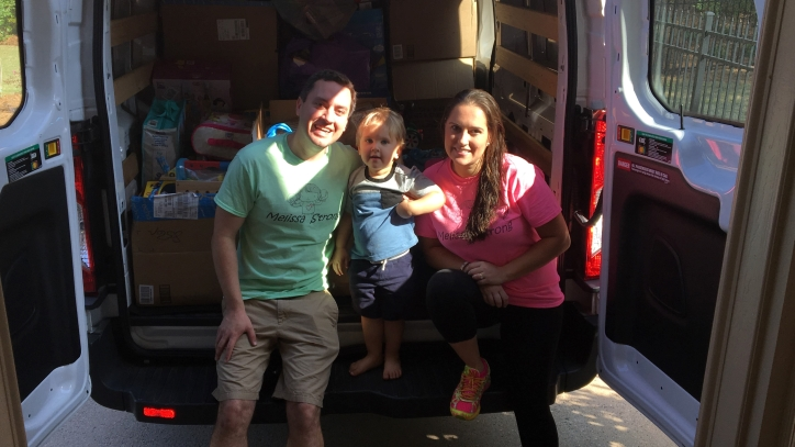 Joe and Erika Depa and their son with a car full of toy donations