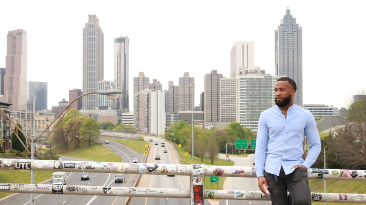 Tony worlds standing on bridge with buildings in background